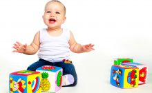 cute happy baby sitting on the floor and playing with toys