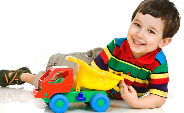 Smiling little boy plays with toy car