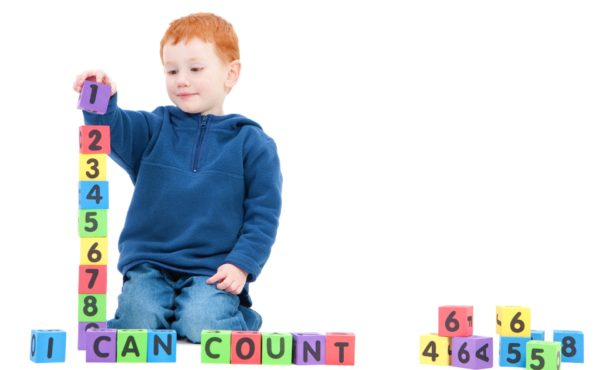 Boy counting numbers with blocks and saying I can count. Isolated on White
